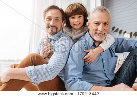 Family bounds. Nice delighted cute boy hugging his dad and grandfather and looking at you while standing behind them