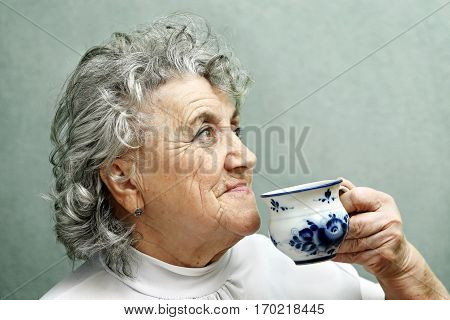 Grandmother drinks with blue cup on a grey