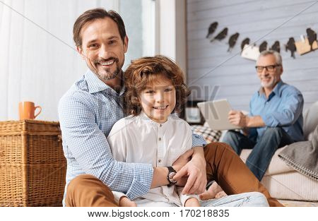 Happy family. Positive pleasant delighted man sitting behind his son and hugging him while looking at you