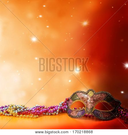 Traditional female carnival venetian mask  on table .Masquerade  mask on  glitter background.Mardi Gras.