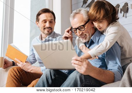 Here is it. Pleasant cute nice boy hugging his grandfather and pointing at the laptop screen while standing behind him