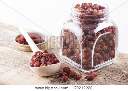 Dried rosehip berries in glass jar on old wooden table