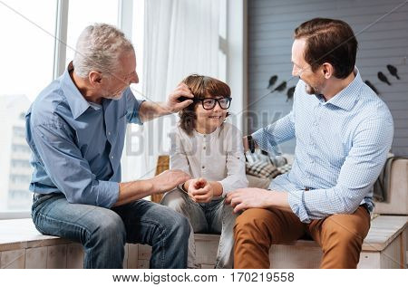Showing care. Nice aged positive man sitting next to his grandson and looking at him while fixing his glasses