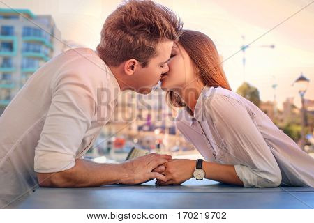 Lovely teenagers kissing by the table
