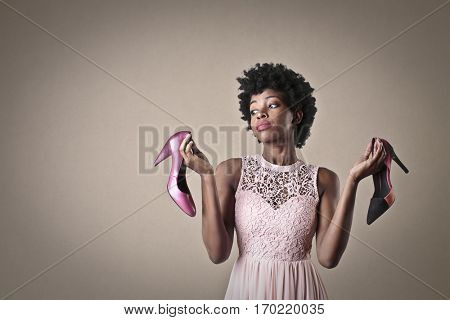 Black girl in nice dress having difficulties to chose the right shoes