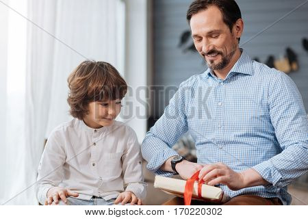 Lets look. Delighted handsome bearded man holding a present and opening it while sitting together with his son