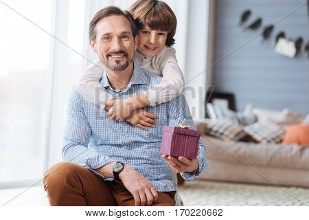 What a surprise. Handsome joyful delighted man smiling and holding a gift box while being hugged by his child