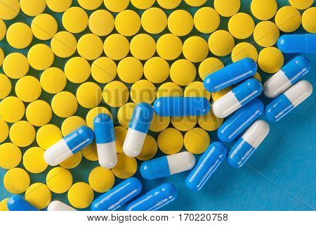 Pile Of Yellow Medical Pills On Blue Background