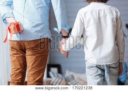 Giving presents. Pleasant handsome adult man holding the hand of his son and hiding a gift behind his back while intending to make a surprise