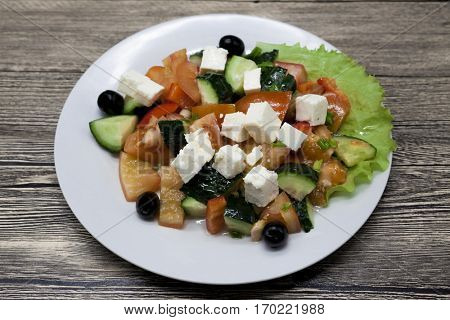 Fresh and juicy Greek salad on a white plate on a wooden table. Can be used as a photo for restaurant menus, bistro. European, Mediterranean cuisine.