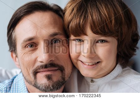 Family portrait. Portrait of happy delighted nice father and son standing together and smiling while looking at you