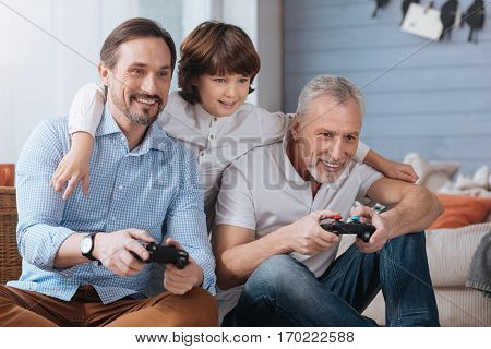 Family entertainment. Delighted happy adult man holding game consoles and playing video games while having fun together