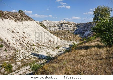 View on hills and fields from a limestone cliff at a quarry under a beautiful blue sky, abandoned white stone career, in fetesti village, Moldova