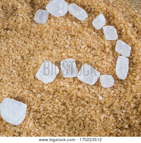 The question mark written with white crystalline sugar (candy) into a pile of brown sugar crystal Demerara.