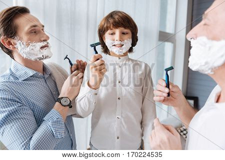Shaving together. Nice delighted joyful men holding razor and looking at each other while shaving together