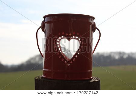 Small red metal bucket with round perforations in the form of a heart, in bucket stands a transparent empty glass, on brown wooden post, in the background green meadow, forest of Krählingen radiate blue sky In the sun in February 2017 in Häselingen