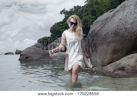 portrait of woman in white dress getting through the water