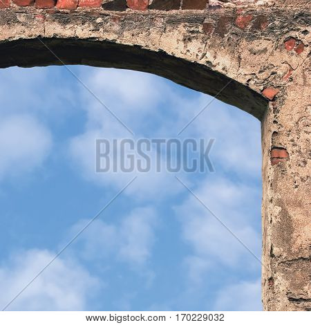 Barn gate door arch stone wall closeup, vertical bright white clouds, sky copy space background, plastered grunge red brick stonewall, old aged beige lime plaster texture, natural bricks brickwork ruins