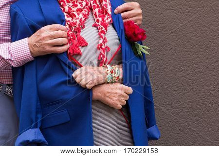 Old man threw his jacket on the shoulders of an old woman. Hands close-up.