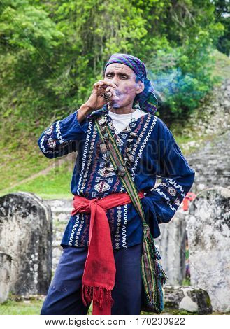 TIKAL, GUATEMALA - DEC 21, 2015: Unidentified Mayan smoking cigar on December 21, 2015  in Tikal, Guatemala. Traditional Mayan fire ceremony at the 2015 new year celebrations.