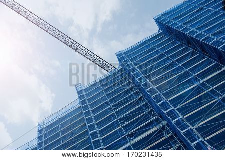 A crane in a construction work. Tall scaffold structure from below. Empty copy space for Editor's text.