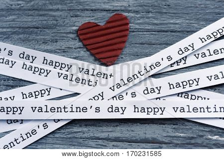 a red heart made of corrugated paperboard and some strips of paper with the text happy valentines day written in it, on a gray rustic wooden background