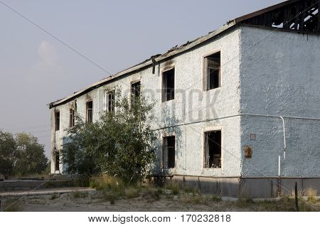 Burnеd light blue two-storeyed building with green trees. After fire