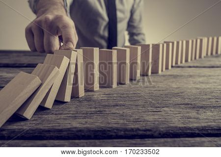 Retro vintage style image of a businessman stopping domino effect. Saving business concept.