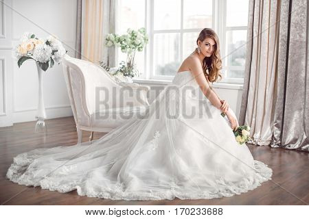 Wedding. Bride in beautiful dress sitting on sofa indoors in white studio interior like at home. Trendy wedding style shot in full length. Young attractive caucasian brunette model like a bride against big window tender posing.