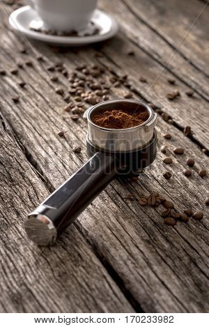 Close up view of coffee machine filter holder with flavored ground coffee beans and white cup with saucer in background on old rough wooden table surface.