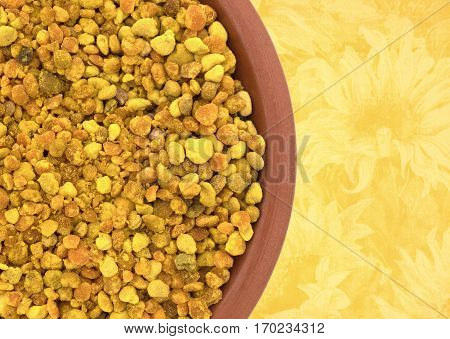 Top close view of organic bee pollen granules in a small bowl atop a yellow floral tablecloth.