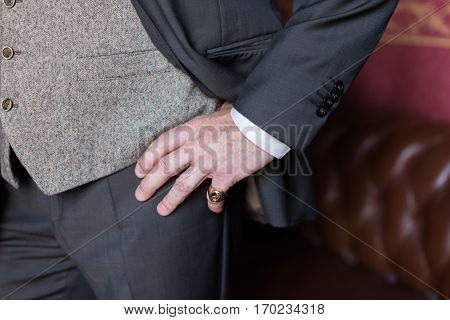 Closeup stylish man in gray suit. Man's hand with a ring on the little finger