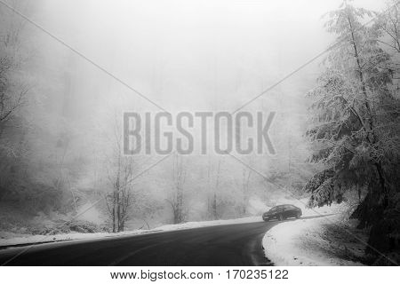 Road in the fog. Mysterious Way. Snowy mountain road. Risk of ice.