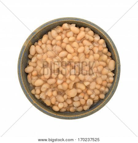 Top view of a serving of organic navy beans in an old stoneware bowl isolated on a white background.