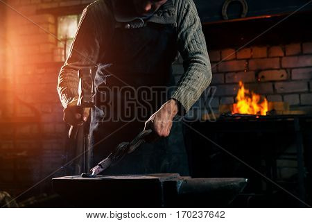 The blacksmith manually forging the molten metal on the anvil in smithy with spark fireworks
