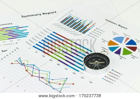 Bussiness graphs and finances with a compass lying nearby.