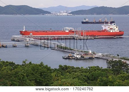 aerail view of Big red boat unloading cargo at dock pier