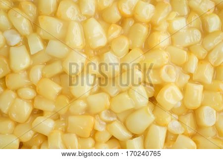 A very close view of shoepeg white corn in a butter sauce.
