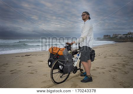 Adventure Cyclist With Bicycle On Beach