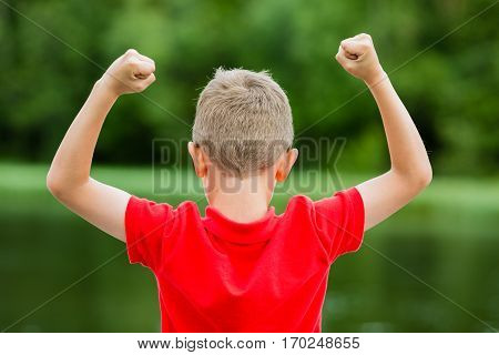 Boy raising his hands in the air and showing his excitement for success or victory.