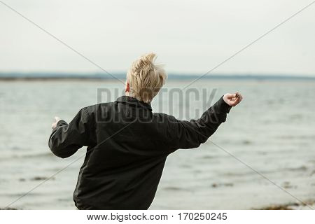 Rear View Of Boy Throwing Something Toward Lake
