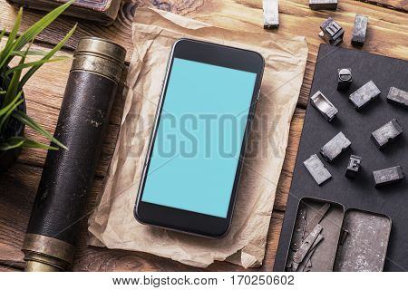 Top view smartphone mock-up on table, with spyglass, plant and so on. Clipping path