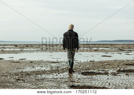 Rear View On Single Blond Boy Walking On Beach
