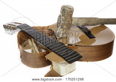 An acoustic guitar that has been smashed with a sledgehammer by its frustrated guitarist owner. No more music practice.
