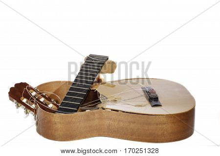 An broken classical acoustic guitar left in bits and pieces by its disillusioned musician owner Now a really rubbish guitar. White background with copy space.