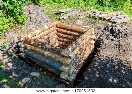 Construction new wooden water well in russian village in summertime