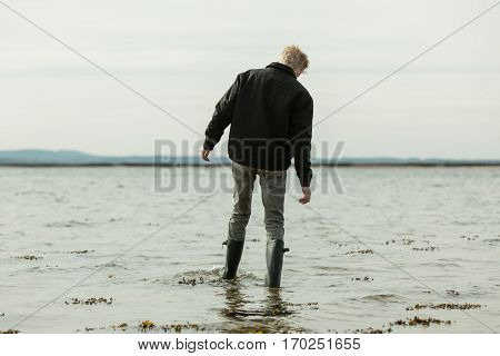 Boy Wading In Water Moving In During High Tide