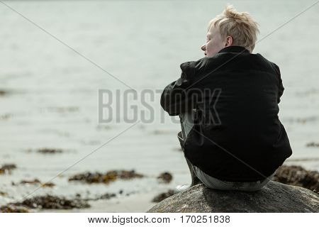 Boy Looking Sideways While Seated On Boulder