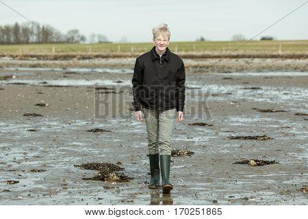 Boy Walking Through Mud On Beach During Low Tide