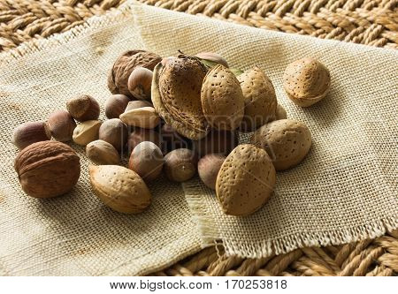 pistachios almonds walnuts on the table. background straw and old cloth. retro. straw  background